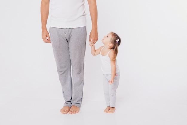 Nettes baby, das lernt, zu gehen und seine ersten schritte zu machen. mutter hält seine hand. kinderfüße hautnah, kopie, raum
