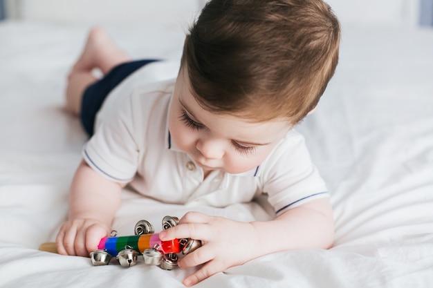 Nettes baby, das mit buntem pastellrassel-rasselspielzeug spielt.