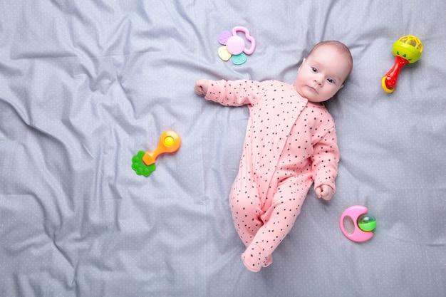 Nettes baby, das mit buntem rasselspielzeug spielt. neugeborenes kind, kleines mädchen, das in die kamera schaut und krabbelt.