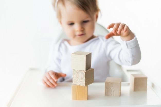 Nettes baby, das mit holzwürfeln spielt. kleiner kinderbauturm. baustein für kinder. montessori-erziehungsmethode. selektiver fokus