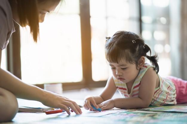 Nettes baby, das mit ihrer mutter am haus malt