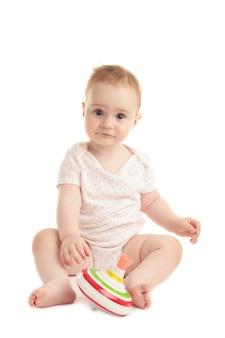 Nettes baby, das sitzt und spielt mit einem spielzeug lokalisiert auf weißem hintergrund