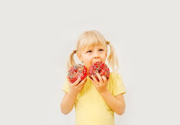 Nettes baby, das süße donuts auf hellem hintergrund isst.