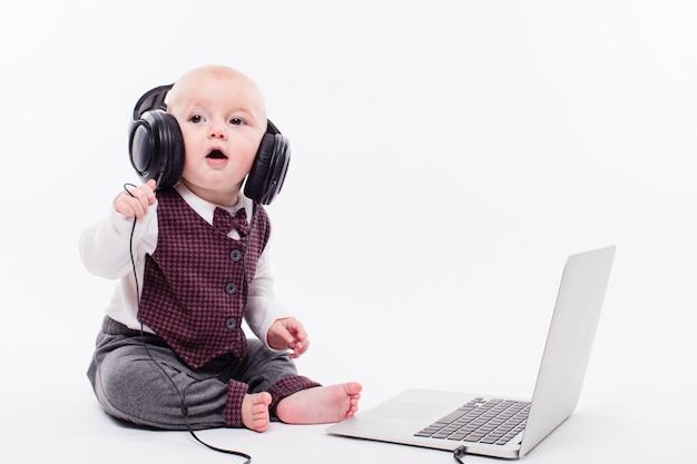 Nettes baby, das vor tragenden kopfhörern eines laptops sitzt