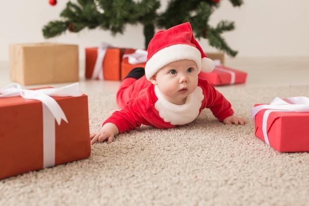 Nettes baby, das weihnachtsmannanzug trägt, der auf boden über weihnachtsbaum kriecht