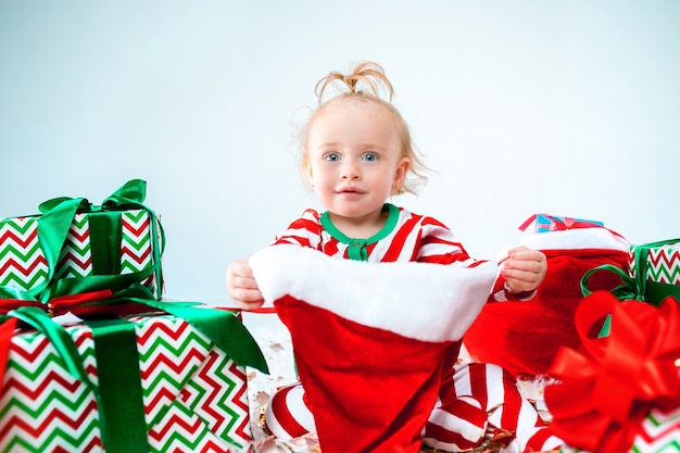 Nettes baby, das weihnachtsmütze trägt, die über weihnachtsdekorationen mit geschenken aufwirft. mit weihnachtskugel auf dem boden sitzen. ferienzeit.