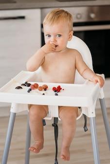 Nettes baby der vorderansicht im hochstuhl, das wählt, welche frucht zu essen