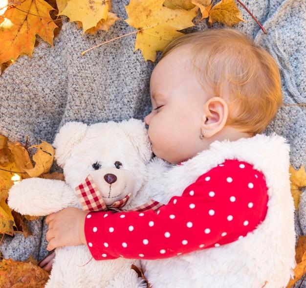 Nettes baby des mittleren schusses, das mit spielzeug schläft