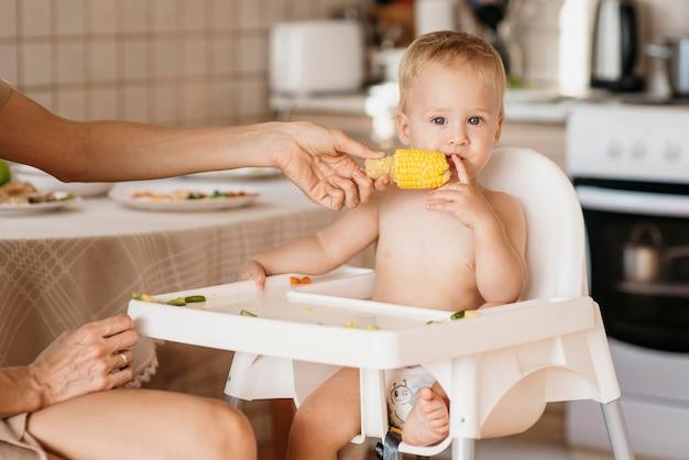 Nettes baby im hochstuhl, der mais isst