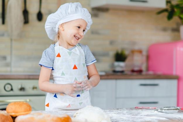 Nettes baby im kostüm kocht, das in der küche kocht
