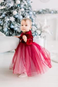 Nettes baby im roten kleid, das nahe dem stuhl auf dem hintergrund des weihnachtsbaumes steht