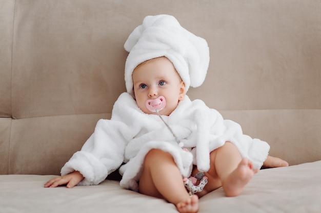 Nettes baby im weißen bademantel