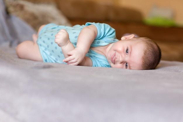Nettes baby in den blauen kleidern, die auf der couch liegen und lächeln.