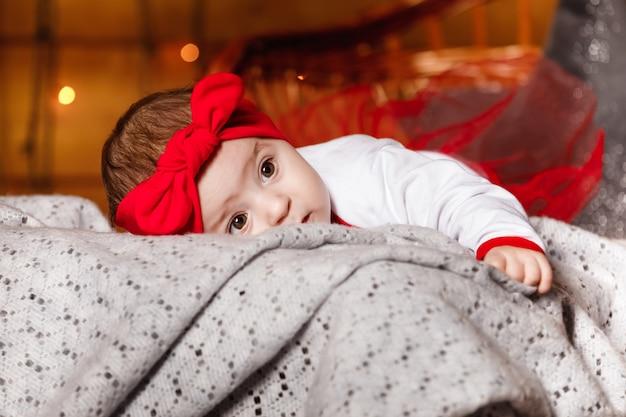 Nettes baby in der roten schleife auf kopf und im weißen pullover, der auf decke, ein weihnachtshintergrund in einem studio mit weihnachtslandschaft liegt.