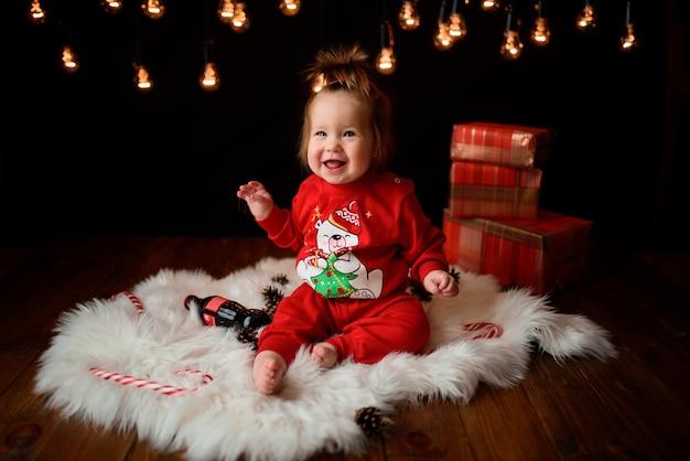 Nettes baby in einem roten weihnachtskostüm mit retro-girlanden sitzt auf einem fell