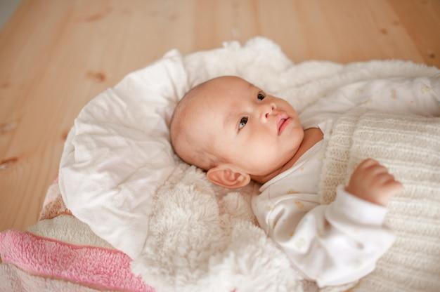 Nettes baby in einem schlafzimmer des weißen lichtes neugeborenes baby ist nett. in bettwäsche für kinder geboren - bilder