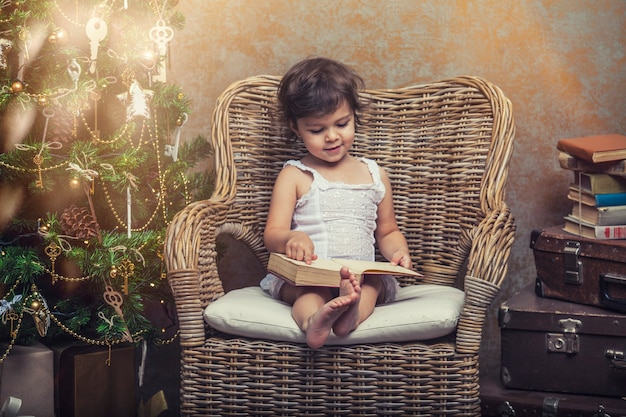 Nettes baby in einem stuhl, der ein buch in einem weihnachtlichen retro-interieur liest