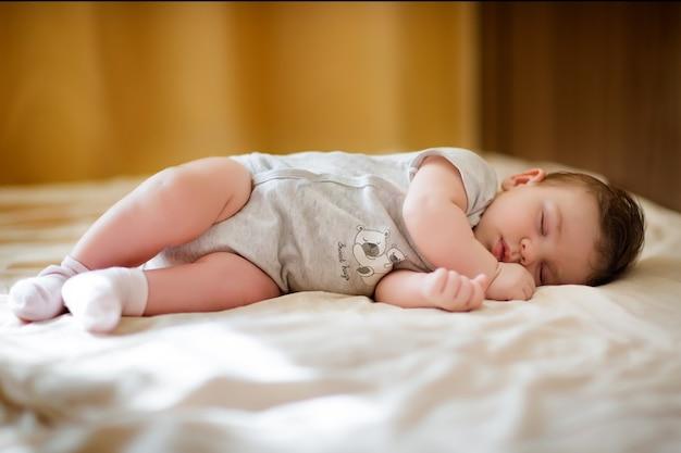 Nettes baby in hellen kleidern, die auf der couch liegen und schlafen.