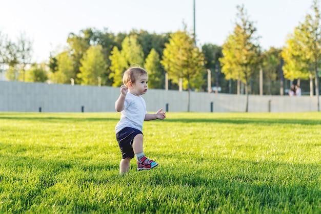 Nettes baby läuft auf einem grünen rasen, der in der natur an einem sonnigen tag spielt.
