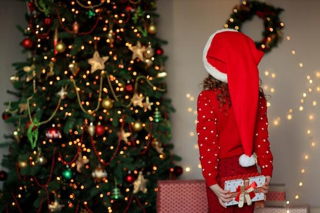 Nettes baby mit einem geschenk nahe dem weihnachtsbaum