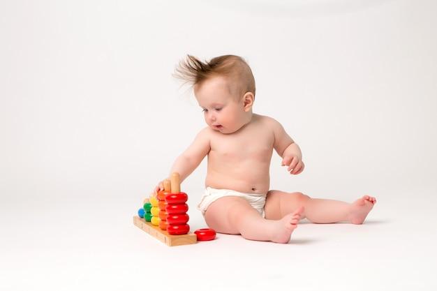 Nettes baby mit entwicklungsspielzeug auf einem weißen hintergrund