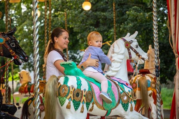 Nettes baby mit mutter auf dem pferd des alten retro-karussells prag tschechien