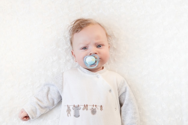Nettes baby mit schnuller auf einer weißen decke