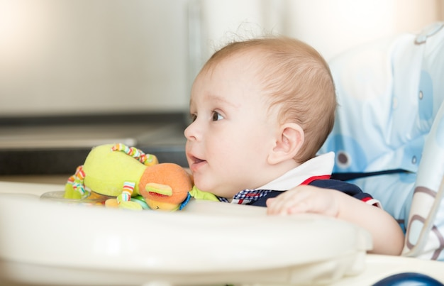 Nettes baby mit schnuller, das auf das frühstück im hochstuhl wartet