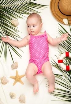 Nettes baby mit strandaccessoires. urlaub auf see mit baby, sommerkonzept