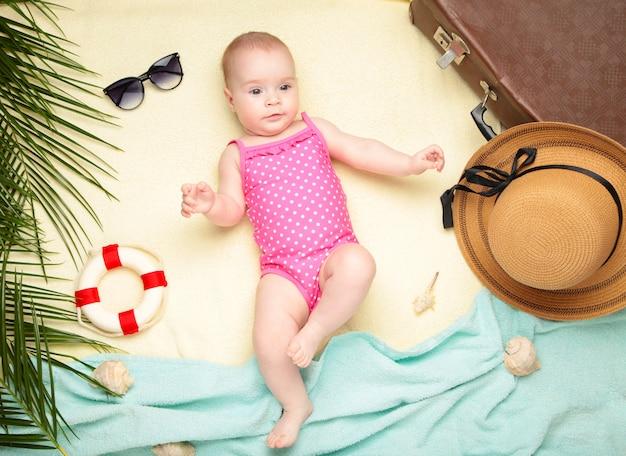 Nettes baby mit strandzubehör auf hellem hintergrund. urlaub auf see mit baby, sommerkonzept