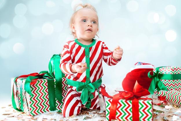 Nettes baby nahe der weihnachtsmannmütze, die über weihnachtshintergrund aufwirft. mit weihnachtskugel auf dem boden sitzen. ferienzeit.