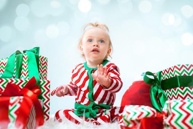 Nettes baby nahe der weihnachtsmannmütze, die über weihnachtshintergrund mit dekoration aufwirft. mit weihnachtskugel auf dem boden sitzen.