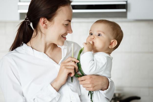 Nettes baby und ihre mutter essen frühlingszwiebeln