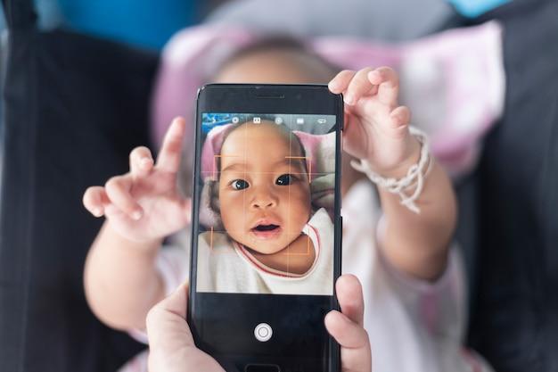 Nettes baby zeigt seine eigenen fotos auf dem smartphone auf dem kinderwagen.