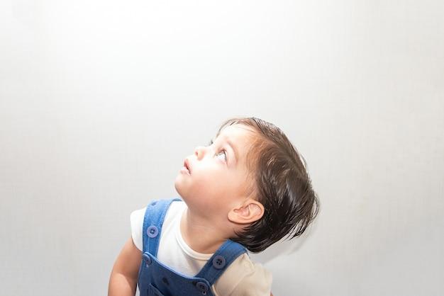 Nettes babyjungenkleinkind mit blauem spielanzug auf weißem hintergrund