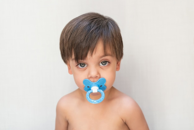 Nettes babykleinkind - mit friedensstifter im mund