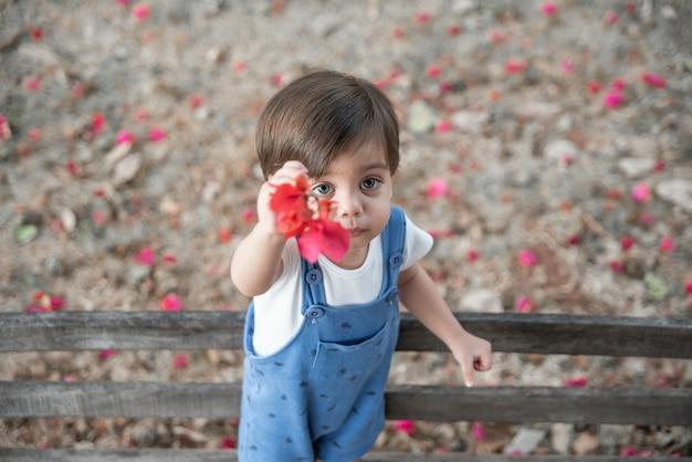 Nettes babykleinkind mit spielanzug - im garten auf der bank, die blume hält