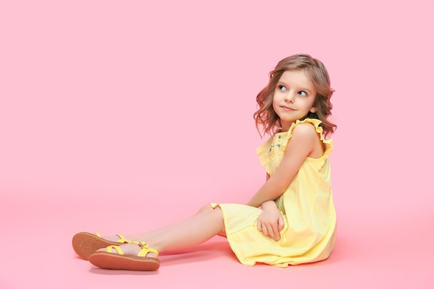 Nettes babymädchen, das ein trendiges gelbes kleid trägt, das im zimmer über rosa sitzt