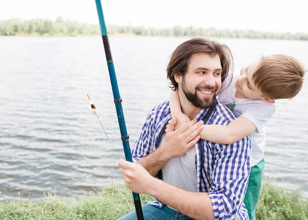 Nettes bild des bärtigen vatis und seines kleinen sohns, die zusammen zeit verbringen. junge umarmt seinen vati, während mann sohn lächelt und betrachtet. sie sind glücklich.