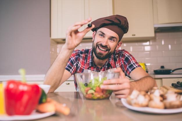 Nettes bild des mannes steht und beugt sich zum tisch. er hält schwarze olive in einer hand und hält eine andere auf schüssel. der mensch sieht glücklich und zufrieden aus.