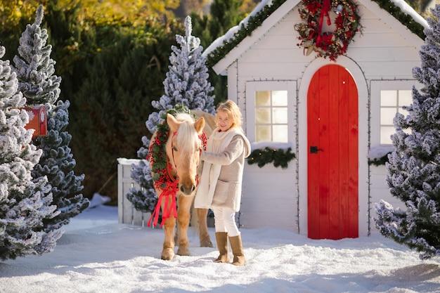 Nettes blondes gelocktes kind und entzückendes pony mit festlichem kranz nahe dem kleinen holzhaus
