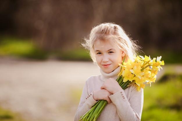 Nettes blondes glückliches kleines mädchen mit gelbem land der narzissen im frühjahr