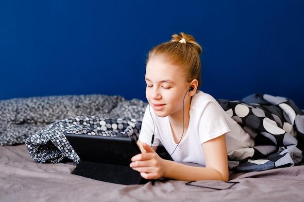 Nettes blondes jugendlich mädchen, das video auf smartphone o ansieht