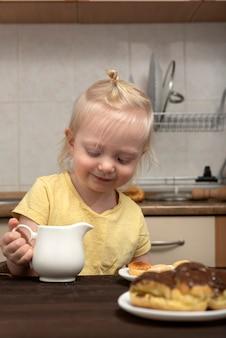 Nettes blondes kind frühstückt in der küche. kleines mädchen, das tee mit süßigkeiten trinkt.