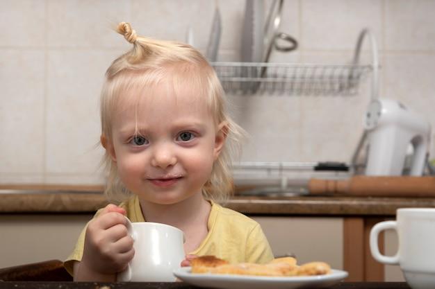 Nettes blondes kind mit tasse in den händen in der küche. frühstück mit kind. kleines mädchen trinkt eine milch.
