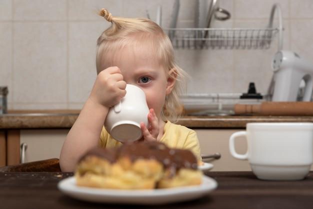 Nettes blondes kind mit tasse in den händen in der küche. kleines lächelndes mädchen trinkt eine milch. frühstück mit kind
