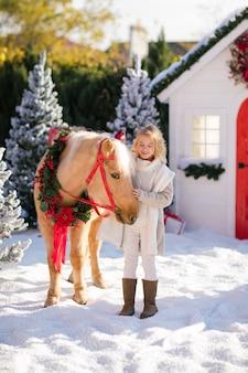 Nettes blondes kind streichelt entzückendes pony mit festlichem kranz nahe dem kleinen holzhaus