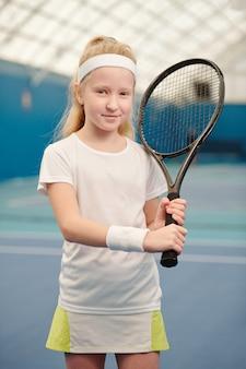 Nettes blondes kleines mädchen in activewear, das tennisschläger gegen die linke schulter hält, während es in stadionumgebung vor der kamera steht