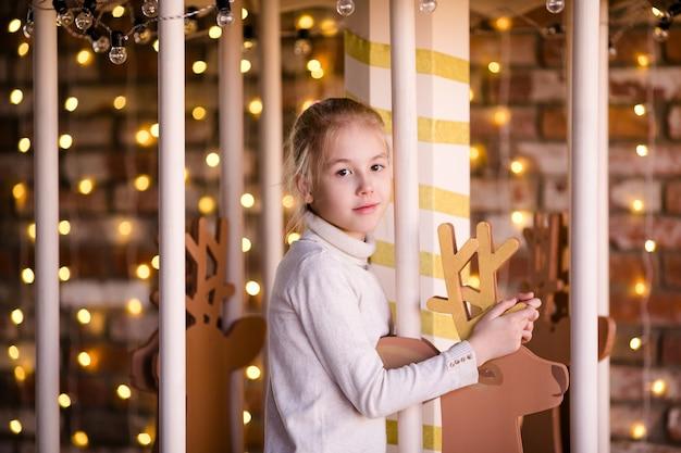 Nettes blondes mädchen auf dem karussell des neuen jahres mit hölzernen rotwild und hellen lichtern