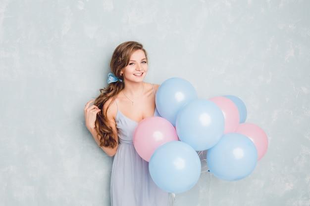 Nettes blondes mädchen, das in einem studio steht, lächelt und blaue und rosa luftballons hält.